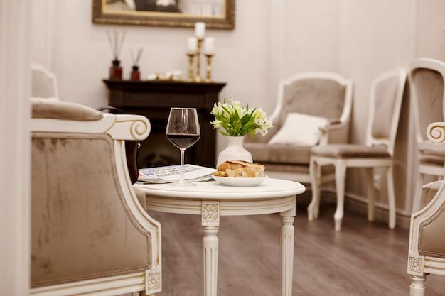 Um copo de vinho tinto, bolos frescos e um vaso de flores brancas estão sentados em cima da mesa na acolhedora sala