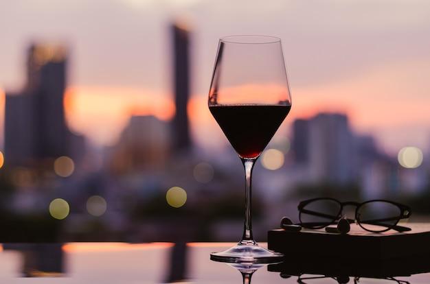 Um copo de vinho tinto com copos e caderno na mesa com o fundo da cidade