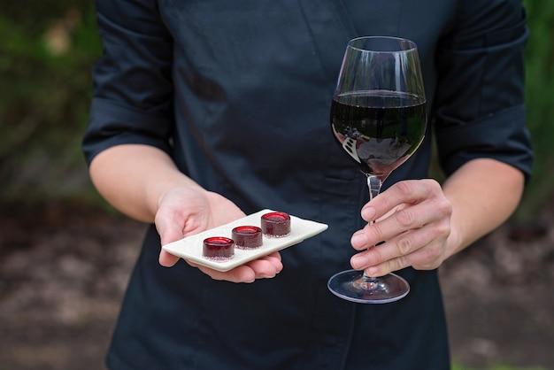 Um copo de vinho tinto e doces de marmelada nas mãos do chef.
