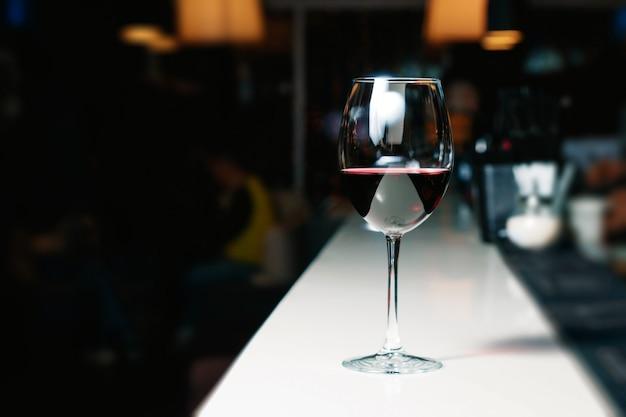 Um copo de vinho tinto em um bar, balcão branco
