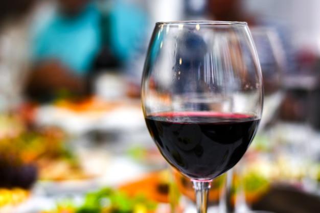 Um copo de vinho tinto fica em uma mesa festiva