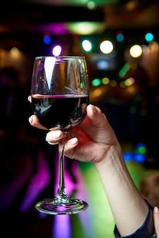 Um copo de vinho tinto na mão de uma mulher jovem.
