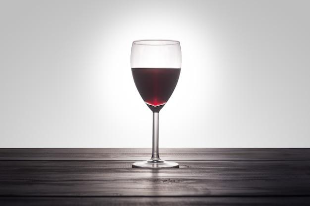 Um copo de vinho tinto numa superfície de madeira