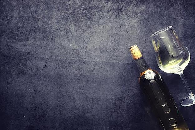 Um copo de vinho tinto seco na mesa. garrafa escura e copo de vinho.