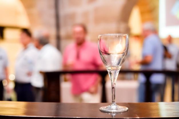 Um copo de vinho vazio em uma mesa de madeira durante um evento, com espaço negativo