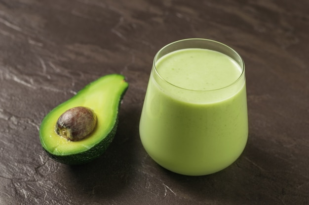 Um copo de vitaminas de abacate e espinafre e meio abacate sobre um fundo de pedra. produto de fitness. nutrição esportiva dietética.