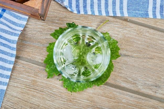 Um copo de wone branco com gelo na mesa de madeira.