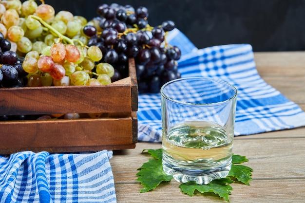 Um copo de wone branco na mesa de madeira com uvas.