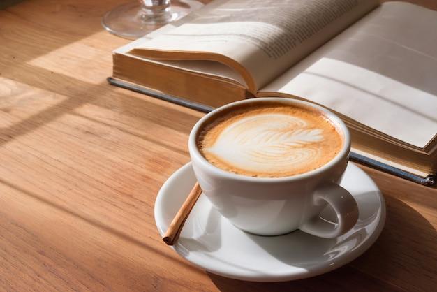 Um copo do café quente da arte do latte na tabela de madeira com o livro no café da cafetaria.