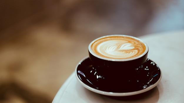 Um copo do café quente do latte com arte do latte da forma do coração, conceito do amante do café