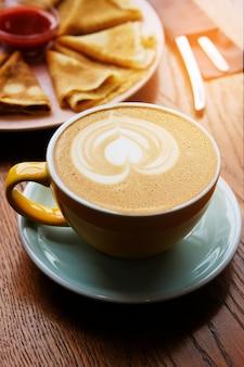 Um copo do cappuccino em uma tabela de madeira no café. coffee break.