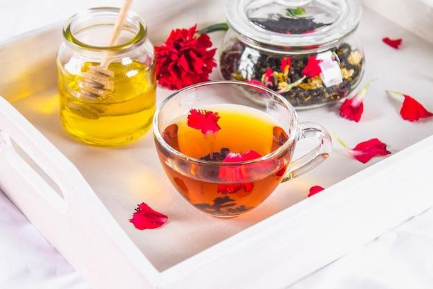 Um copo do chá, uma lata do mel e um frasco da tisana preta em uma bandeja branca na cama.