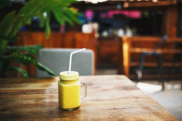 Um copo do smoothie feito recentemente feito dos frutos da cor amarela brilhante, está na tabela do restaurante, em um frasco bonito com uma tubulação, de encontro a um fundo das folhas das palmeiras.