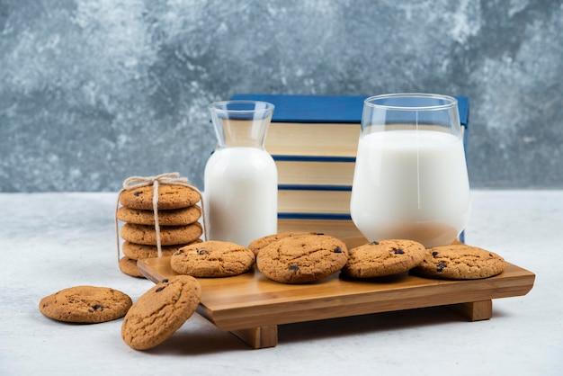 Um copo e um pote de leite com biscoitos deliciosos.
