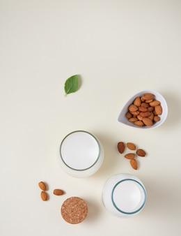 Um copo e uma garrafa de leite de amêndoa vegan fresco e algumas nozes espalhadas sobre um fundo claro. vista superior e espaço de cópia