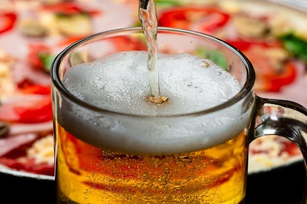 Um copo em que a cerveja é derramada, close-up em um fundo de pizza.