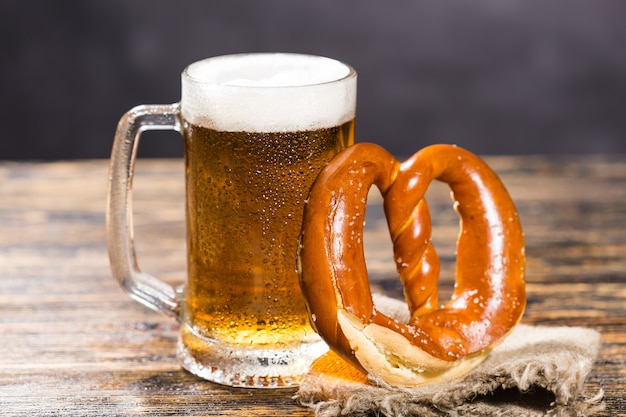 Um copo enorme de cerveja em uma mesa com um bagel