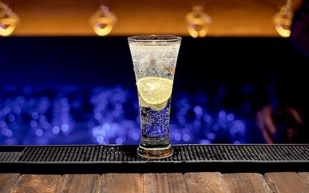 Um copo grande com água com gás e uma rodela de limão dentro, uma boate.