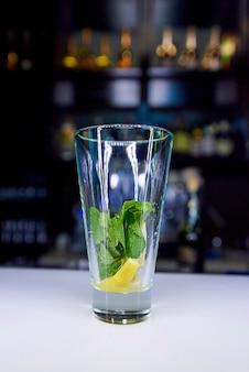 Um copo vazio com uma hortelã e limão na barra.