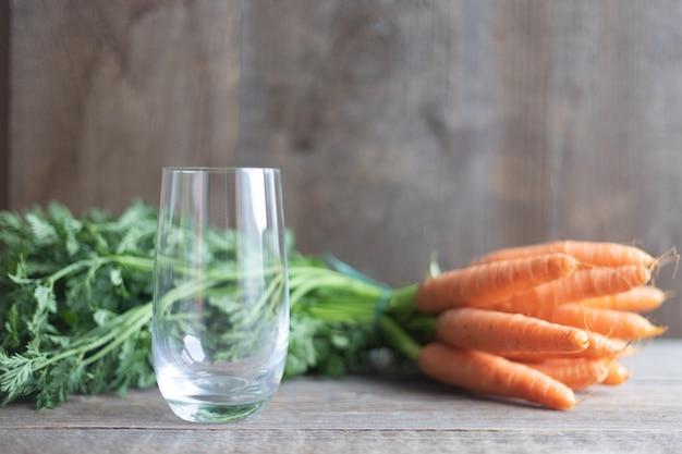 Um copo vazio em uma mesa de madeira e ao lado de um monte de cenouras com tops verdes
