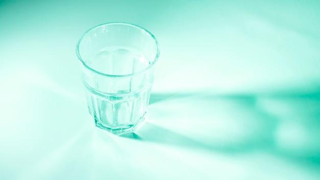Um copo vazio no fundo colorido verde na luz solar