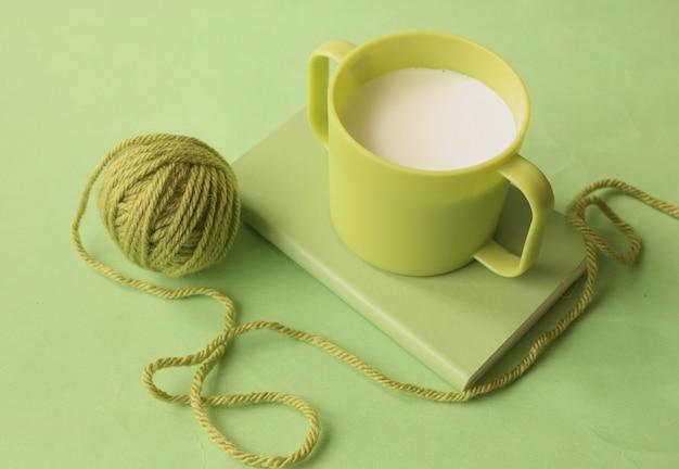 Um copo verde de leite no livro e uma bola de fio verde ao redor.