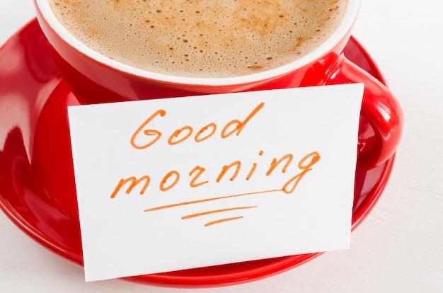Um copo vermelho do bom dia do cappuccino e das notas na tabela rústica leve.