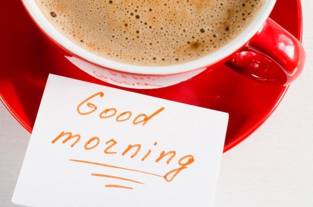 Um copo vermelho do bom dia do cappuccino e das notas.