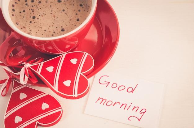 Um copo vermelho do cappuccino com coração de madeira e bom dia das notas.