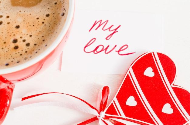 Um copo vermelho do cappuccino com coração de madeira e nota meu amor.