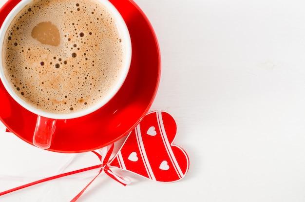 Um copo vermelho do cappuccino com coração de madeira na tabela rústica leve.