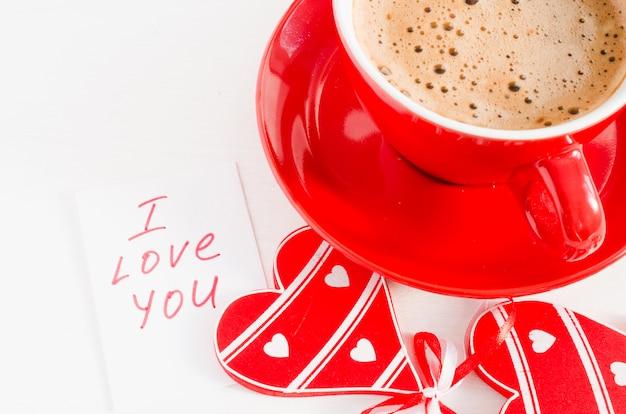 Um copo vermelho do cappuccino com coração e notas de madeira eu te amo.