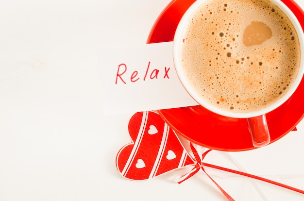 Um copo vermelho do cappuccino com coração e notas de madeira relaxa.