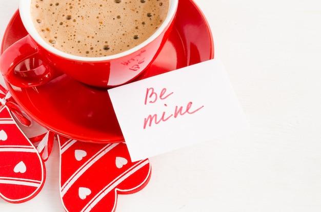 Um copo vermelho do cappuccino com coração e notas de madeira seja meu.