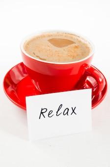 Um copo vermelho do cappuccino e das notas relaxa na tabela rústica leve.