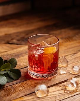 Um coquetel de frutas com cubos de gelo na mesa de madeira marrom.