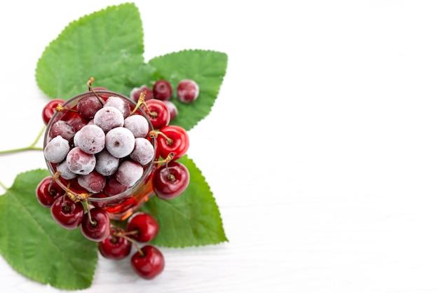 Um coquetel de frutas frescas com gelo de cerejas vermelhas frescas resfriando no branco, beba um coquetel de frutas coloridas