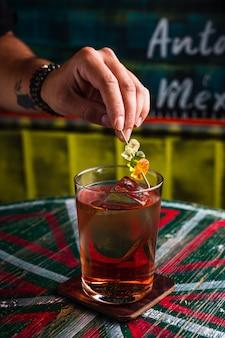 Um coquetel transparente em um copo alto com um grande cubo de gelo. uma mão colocando guarnição de ursinhos de goma em cima de uma bebida