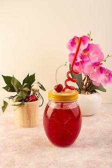 Um coquetel vermelho cereja com canudo dentro de uma pequena lata refrescante em rosa