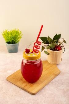 Um coquetel vermelho cereja com canudo dentro de uma pequena lata, resfriando junto com cerejas frescas e planta em rosa