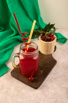 Um coquetel vermelho cereja com canudos dentro de uma pequena lata, resfriando em uma mesa de madeira junto com cerejas frescas em rosa