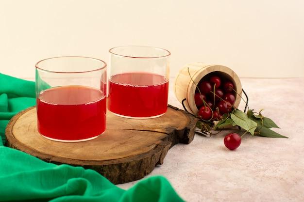 Um coquetel vermelho cereja com vista frontal dentro de pequenos copos refrescando junto com cerejas frescas em rosa