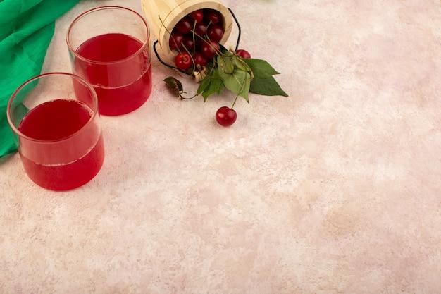 Um coquetel vermelho cereja com vista superior dentro de pequenos copos refrescando junto com cerejas frescas em rosa