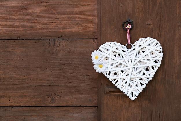 Um coração branco tecido com margaridas pendura em uma parede de madeira.