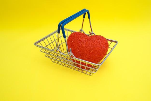 Um coração de acrílico vermelho encontra-se em uma cesta de compras sobre uma mesa amarela.