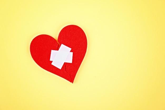 Um coração de feltro vermelho quebrado em duas metades, coladas por um gesso sobre um fundo amarelo.