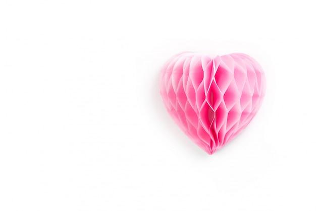 Um coração de papel rosa exuberante em uma superfície branca,