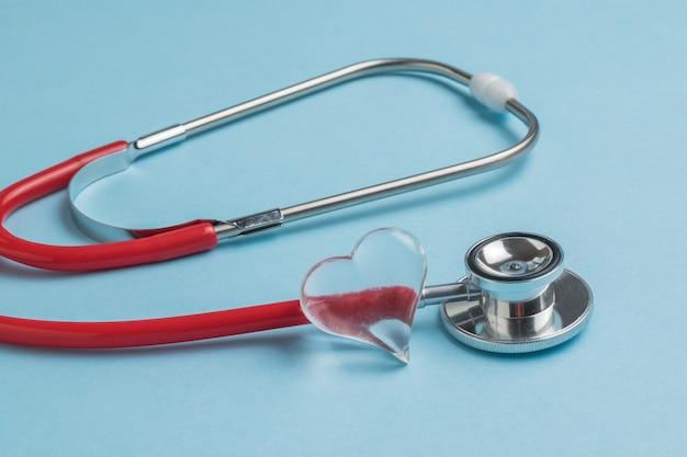 Um coração de vidro e um estetoscópio vermelho sobre um fundo azul. o conceito de tratamento de várias doenças.