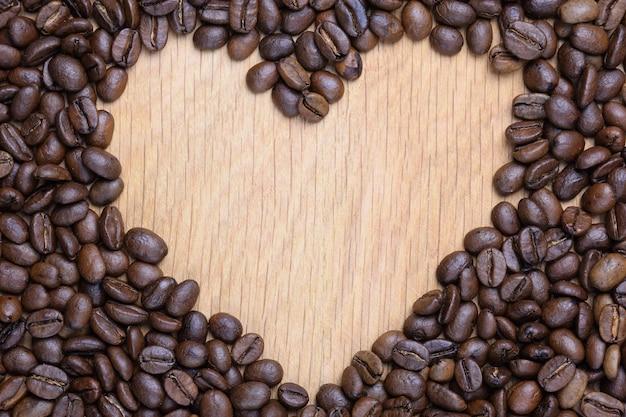 Um coração é colocado em uma superfície de madeira feita de grãos de café. no centro existe um vazio para o