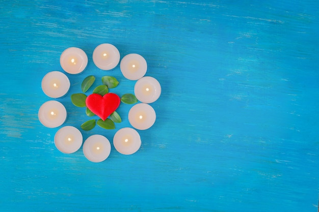 Um coração escarlate e folhas verdes estão rodeados por pequenas velas acesas sobre um fundo azul de madeira.